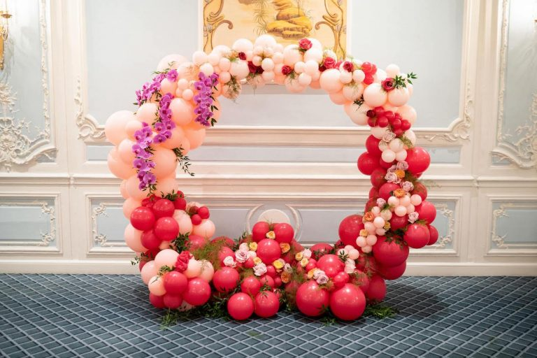 red and pink balloon arch with florals